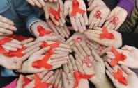 University students hold red ribbons at a photo opportunity during an HIV/AIDS awareness rally on World AIDS day in Chengdu, Sichuan province December 1, 2009. REUTERS/Stringer (CHINA HEALTH SOCIETY) CHINA OUT. NO COMMERCIAL OR EDITORIAL SALES IN CHINA