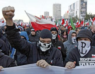 Far-right protesters with faces covered shout slogans during their annual march, which coincides with Poland's national Independence Day in Warsaw November 11, 2013. Polish riot police used rubber bullets on Monday to break up groups of masked far-right youths who threw firecrackers and set fire to parked cars during a nationalist march through the center of the capital. REUTERS/Kacper Pempel (POLAND  - Tags: POLITICS CIVIL UNREST)